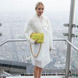 Die deutsche Mode-Bloggerin Leonie Hanne posiert in schwindelerregender Höhe für die Fotografen bei der Show von Coperni. Ein minimalistischer Regenmantel und neongrüne Accessoires von Bottega Veneta machen ihren Look perfekt.