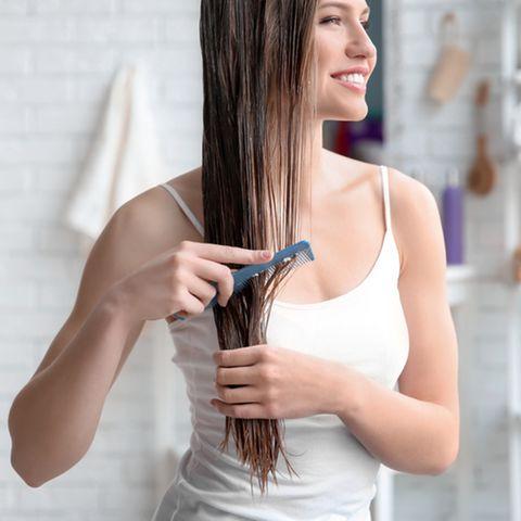 Haaröl ohne Silikone: Frau verteilt Öl in den Haarspitzen.