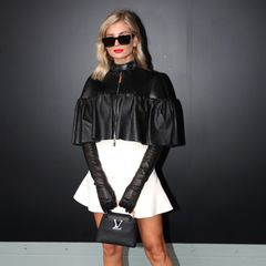 Die Coolness in Person: Xenia Adonts setzt für die Show von Louis Vuitton auf ein schwarzes Leder-Cape und lange Handschuhe. Sonnenbrille und knallroter Lippenstift machen den Glam-Rock-Look perfekt.