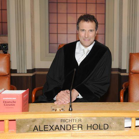 """Alexander Hold sitzt im Fernsehstudio in Münchenin der Kulisse des """"Großen Sitzungssaals"""" derGerichtsshow """"Richter Alexander Hold""""."""