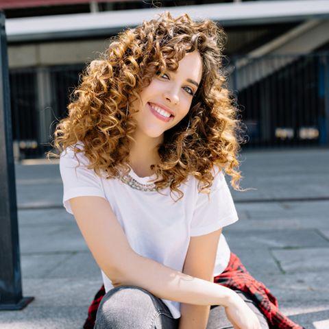Naturlocken Pflege: Lächelnde Frau mit voluminösen Locken