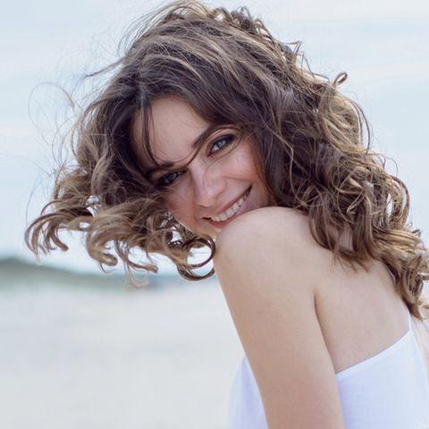 Brüchige Haare: Lächelnde Frau mit lockigen braunen Haaren.