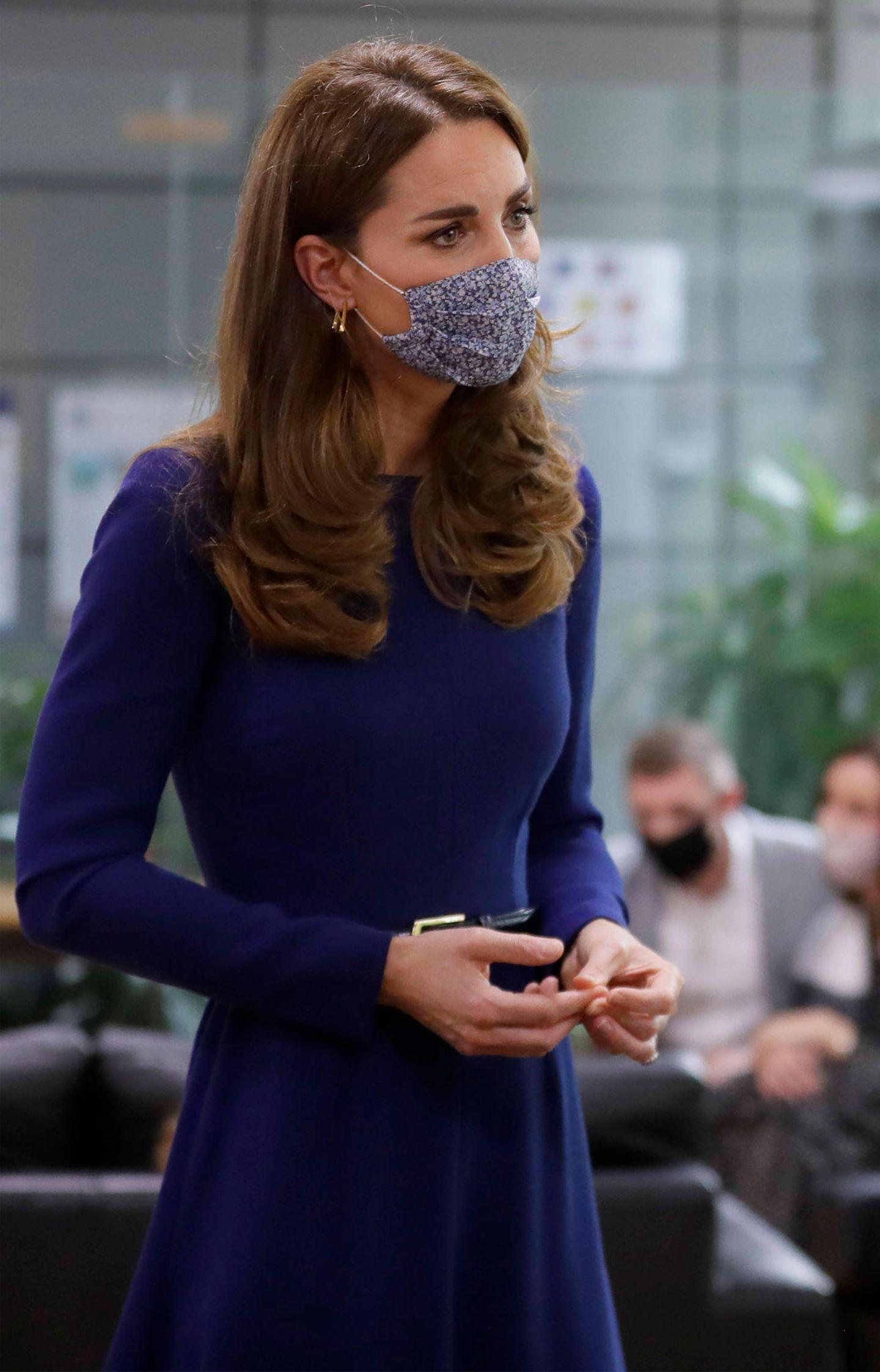 """Dieser Termin dürfte Herzogin Catherine nicht leicht gefallen sein. Am Mittwoch (14. Oktober) besucht die Dreifachmama die Kinder-Charity-Organisation """"Tommy's"""", die Forschungsarbeiten über Tot-, Früh- und Fehlgeburten finanziert und werdende Eltern und jene, die ein solches Drama erleben mussten, unterstützt. Für den Anlass wählte Kate ein schickesMidi-Dress in royalem Blau mit langen Ärmeln. Ihren Look komplettiert sie mit einem schwarzen Taillengürtel und farblich passenden Heels. Das besondereHighlight ihres Looks ist allerdings erst auf den zweiten Blick zu entdecken ..."""
