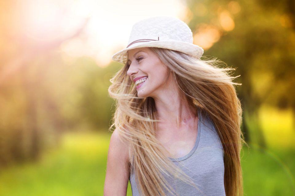 Dickere Haare bekommen: Lächelnde Frau mit langen blonden Haaren und Hut.