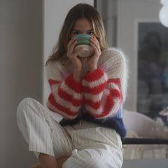 """In einer Nadelstreifen-Hose, einem ausgefallenen Woll-Pullover und einer großen Tasse Tee macht es sich Anna in ihrem Zuhause gemütlich und wappnet sich für die kalte Jahreszeit. Dazu schreibt die Schönheit: """"Feeling warm and cozy""""."""