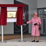 """Wie viele Plaketten, Gedenktafeln und Schilder Queen Elizabeth in ihrer über 68-jährigen Regentschaftenthüllt hat - man weiß es nicht. Was mein weiß ist: Auch nach sieben Monaten Corona-Pause zieht die Queen wie ein Profi am Schnürchen des Vorhangs. Das neue """"Energetics Analysis Centre"""" zum Schutz der Briten vor explosiven Substanzenund Terror ist eröffnet! Das Lachen auf ihrem Gesicht zeigt: Sie freut sich, ihrer royalen Pflicht wieder einmal bei einem Präsenztermin nachkommen zu dürfen.""""Was machen Sie damit?"""" fragt sieGeschäftsführer Gary Aitkenhead über das Schild. Der antwortet, man werde es mit Stolz in der Lobby aufhängen,um an einen großartigen Tag zu erinnern."""