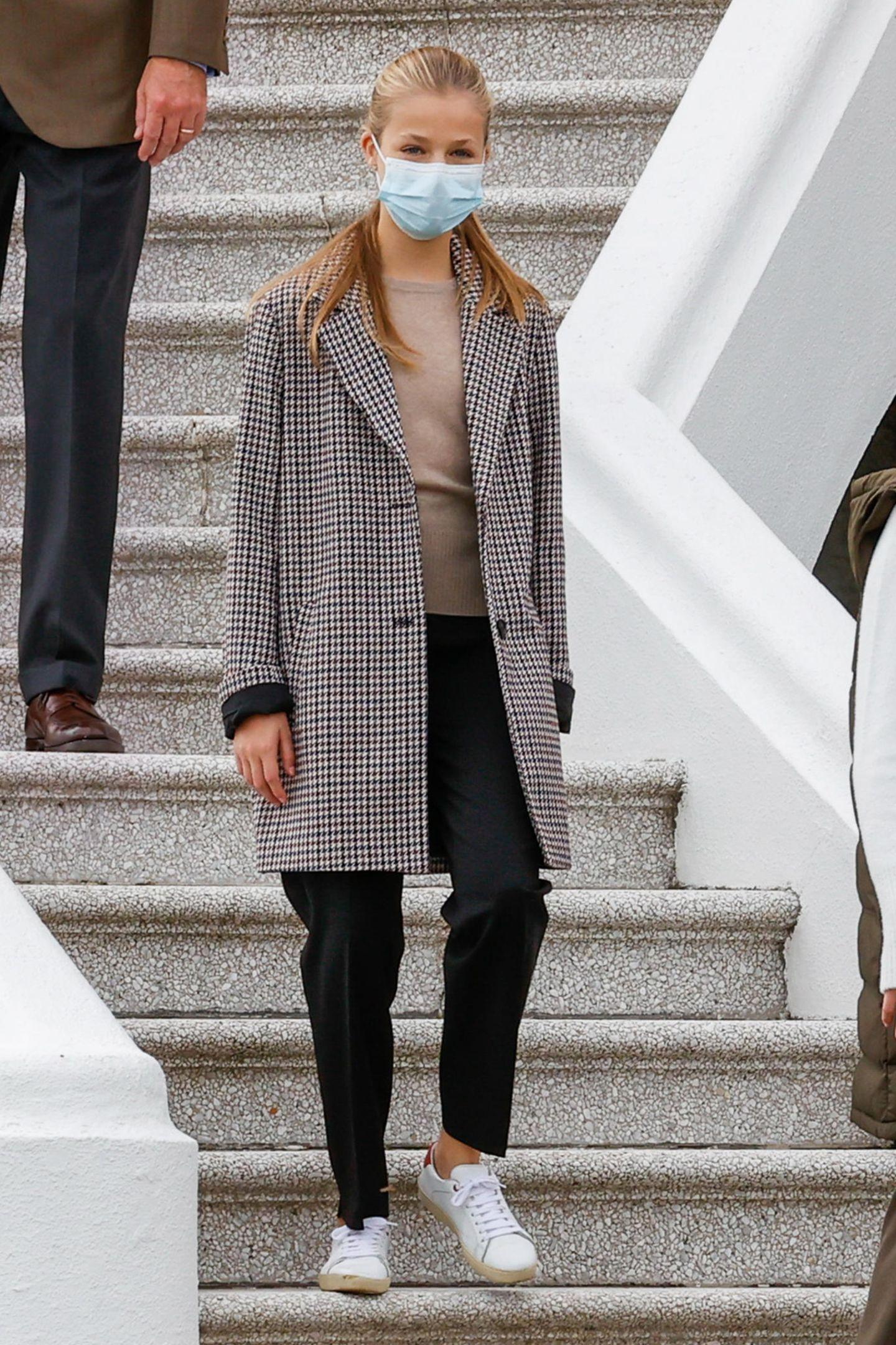 Prinzessin Leonor zeigt sichin einem lässigen Herbst-Outfit: Sie trägt weiße Sneaker, eine dunkle Chino mit Bügelfalte, einen beige-farbenen Wollpullover und einen karierten Mantel mit breitem Revers. Obwohl die 14-jährige Thronfolgerin immer selbstbewusster wird, scheint sie sich diesen eleganten Look bei einer royalen Stilikone abgeschaut zu haben...