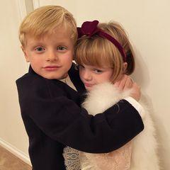 17. Oktober 2020  Auf ihrem Instagram-Profil teilt Fürstin Charlène ein neues Foto ihrer modischen Zwillinge Prinz Jacques und Prinzessin Gabriella. Dabei umarmt der kleine Fürsten-Sohn in seinem dunklen Jackett seine Schwester fest, die scheinbar nicht so viel Lust auf das Foto hat wir ihr Bruder. Gabriella trägt eine weiße Kunstfellweste. Feine Spitze umschmeichelt ihre Arme und ein roter Samthaarreif setzt dem zauberhaften Outfit die Krone auf.