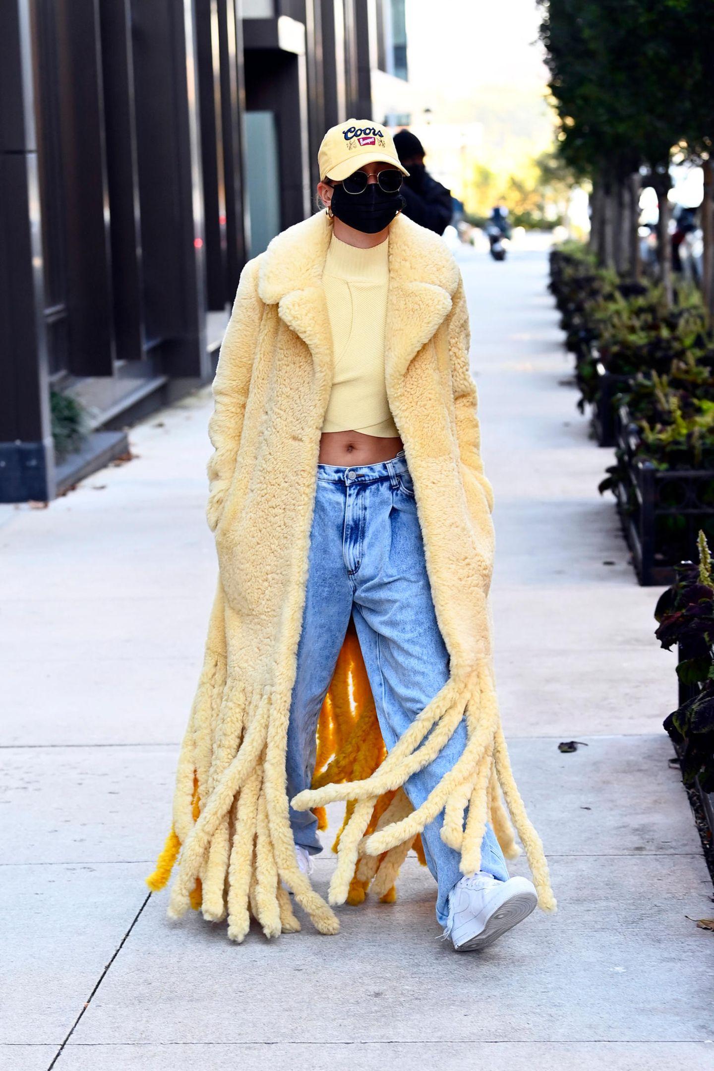 Hailey Bieber mag es lässig. In ihrem Lammfellmantel mit Fransen (von Bottega Veneta, Preis rund 6.900 Euro) trotzt sie dem New Yorker Herbstwetter. Eine baggy Jeans und ein gelbes Crop-Top versprühen Sommerlaune. Dazu trägt sie Cap und Maske und kann so - fast - unerkannt bleiben.