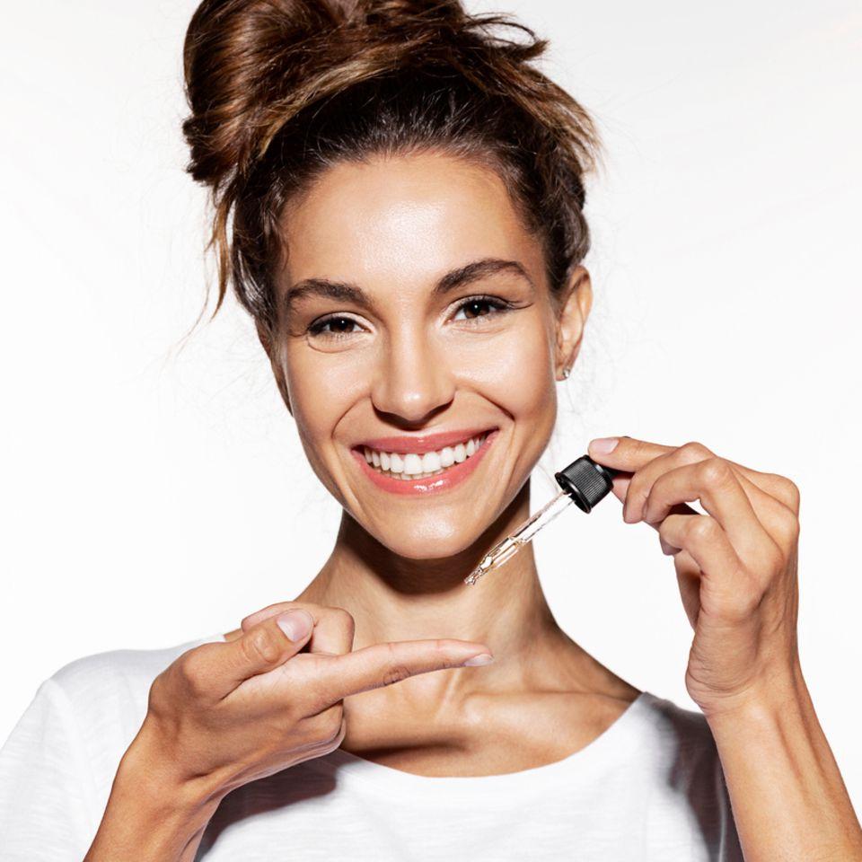 Lächelnde Frau trägt Gesichts-Öl auf den Finger auf