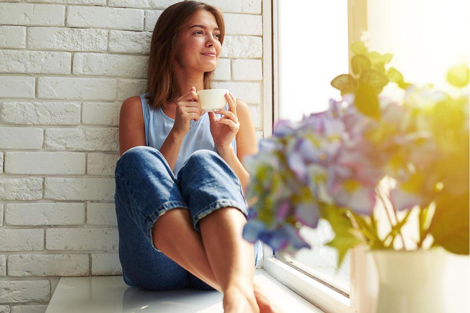 Frau sitzt auf einer Fensterbank