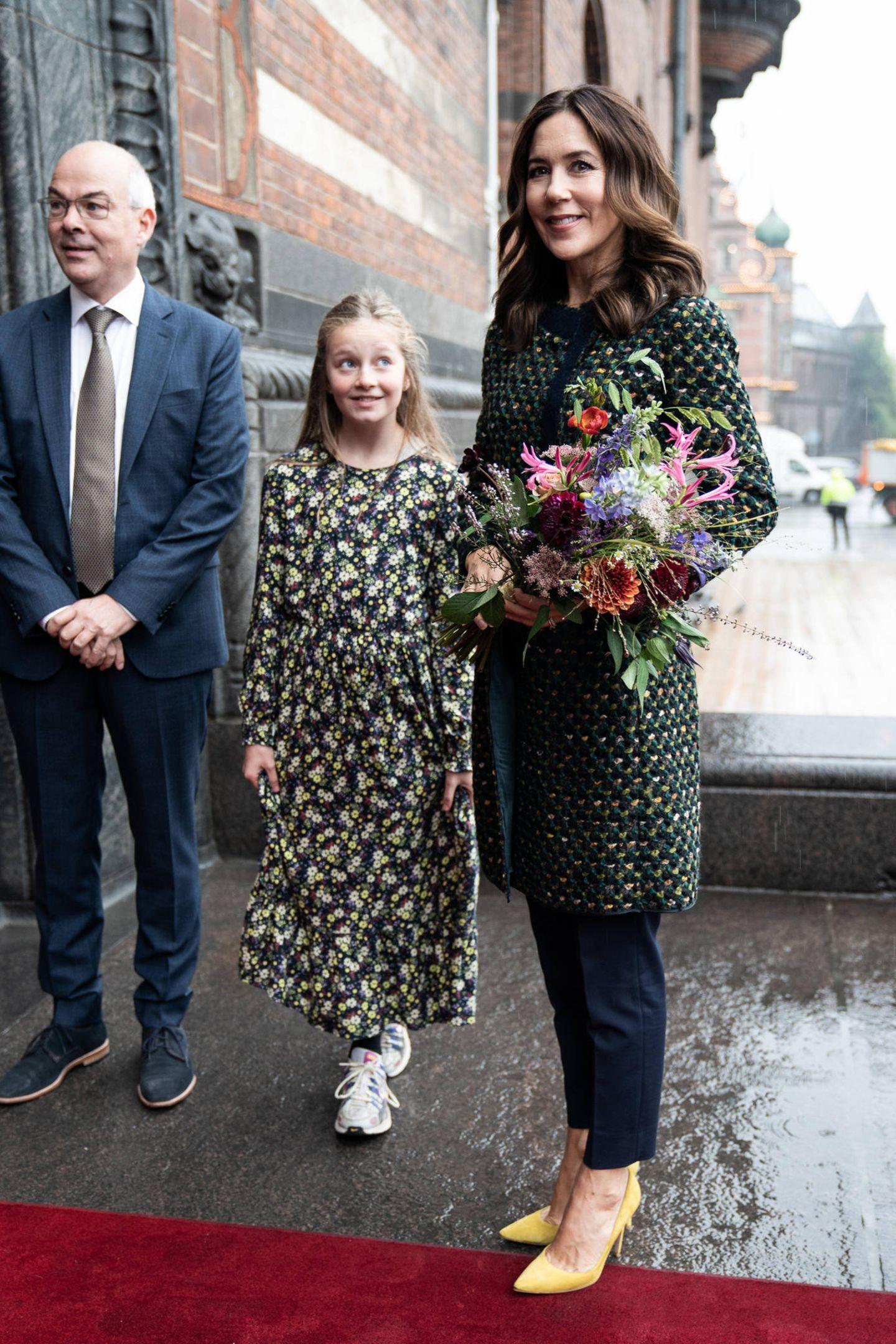 Der Look von Mary begeistert nicht nur das junge Mädchen: Die Kronprinzessin zeigt sich in einem geblümten Mantel von Prada. Dazu trägt sie eine dunkle Hose und senfgelbe Pumps.