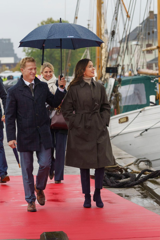 Dem dänischen Herbstwetter trotzt Prinzessin Mary in einem langen karierten Mantel, zusätzlichen Schutz bietet auch der Regenschirm, der netterweise für sie gehalten wird. Rollkragenpullover, eine dunkle Hose und Wildleder-Boots machen die Kombi perfekt.