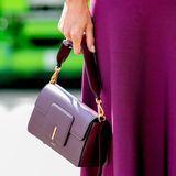 """Die dunkel lilafarbene Tasche, die sie lässig in der Hand hält, stammt vom jungen niederländischen Label Wandler. Die """"Georgia""""-Schultertasche mit goldener Hardware kostet rund 675 Euro und ist dank seines cleanen Designs zeitlos und elegant."""