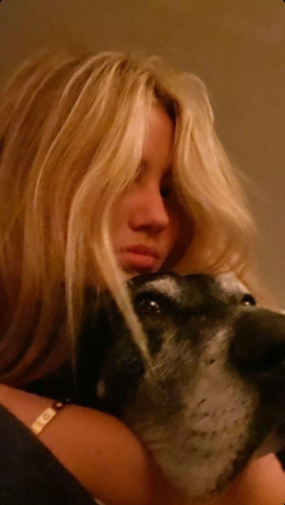 """Heidi Klums Tochter Leni kuschelt mit Hund Anton. An ihrem Handgelenk funkelt das berühmte """"Love Bracelet"""" von Cartier."""