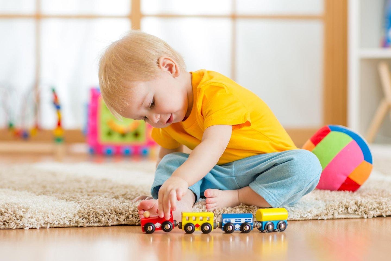 Kinderspielzeug, 2-Jähriger, Holzeisenbahn für Kinder, Junge spielt mit Holzbahn