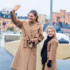 """Was für ein Duo:Victoria und Estelle zeigen sich bei der Einweihung der """"Slussbron"""" in Stockholm im perfekten Partnerlook. Beide tragen beigefarbene Mäntel, bei Victoria ist auch der Rest des Outfits beige, bei Estelle dagegen schwarz."""