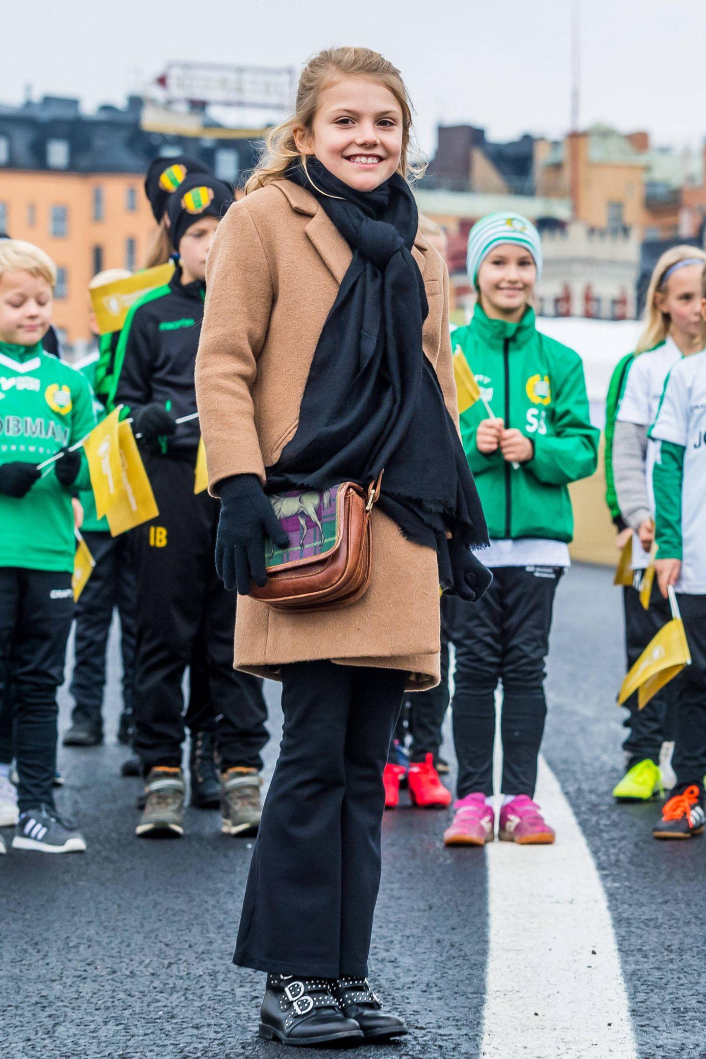 """Prinzessin Estelle ist mir ihren acht Jahren schon ein großes Fashion-Vorbild. Im Camel-Coat und mit schwarzer Schlaghose strahlt siebei der Einweihung der Schleusenbrücke """"Slussbron"""" in Stockholm. Doch so erwachsen ihr Look auf den ersten Blick auch scheinen mag: Mit ihrer niedlichen Pferde-Tasche gibt Estelle dem Outfit ihre ganz eigene Note und macht dieherbstliche schwarz-beige-Kombination zum Hingucker."""