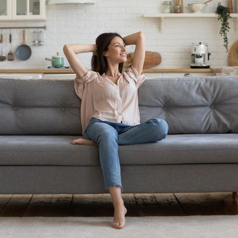 Frau sitzt zufrieden auf dem Sofa