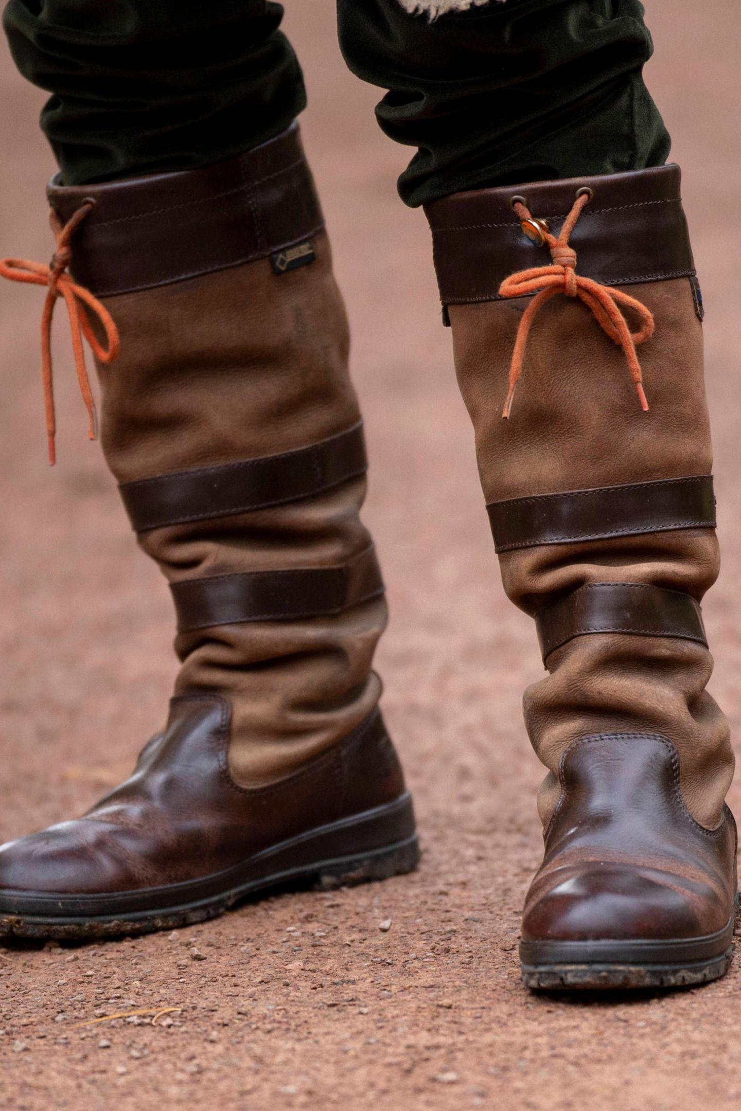 """Der Stiefel """"Galway"""" des TraditionslabelsDubarrybesticht insbesonderedurch seinenGlatt- und Rauleder-Mix in der Farbe Dunkelbraun sowie durch eineorangefarbeneSchnürung unterhalb des Knies. Royals und Naturfreunde lieben den Allwetter-Schuh für rund 380 Euro. So zeigt sich beispielsweise Herzogin Kate ...."""