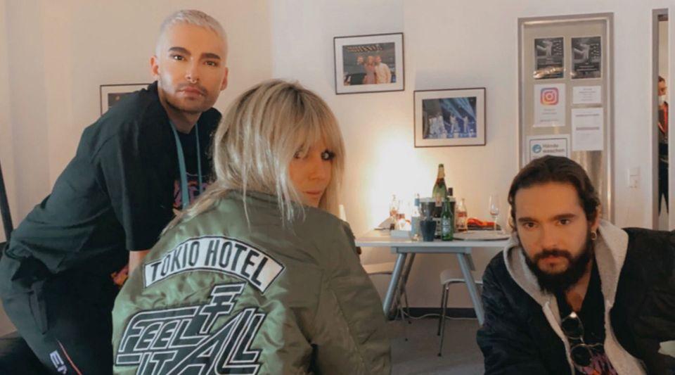 """Anfang Oktober hat die Band """"Tokio Hotel"""" ihren Erfolgsschlager """"Durch den Monsun"""" noch einmal neu aufgenommen. Promotet wird seitdem nicht nur auf auf den Social-Media-Seiten der Bandmitglieder, sondern auch bei Toms Ehefrau Heidi Klum. Sie zeigt sich in ihrer Instagram-Story ineinerolivgrünen Bomberjacke mit der Aufschrift desSongtitels der Band: """"Feel it All"""". Einen weiteren """"Fangirl-Moment"""" des Models hält Bill Kaulitz in seiner Story fest ..."""