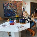 In der Mitte des Raumes steht ein asymmetrischer Esstisch, den Claudia Schiffer herbstlich dekoriert hat. Die bunten Vasen sowie die stylischen Coffee-Table-Books lassen das Wohnzimmer gleich gemütlicher wirken.