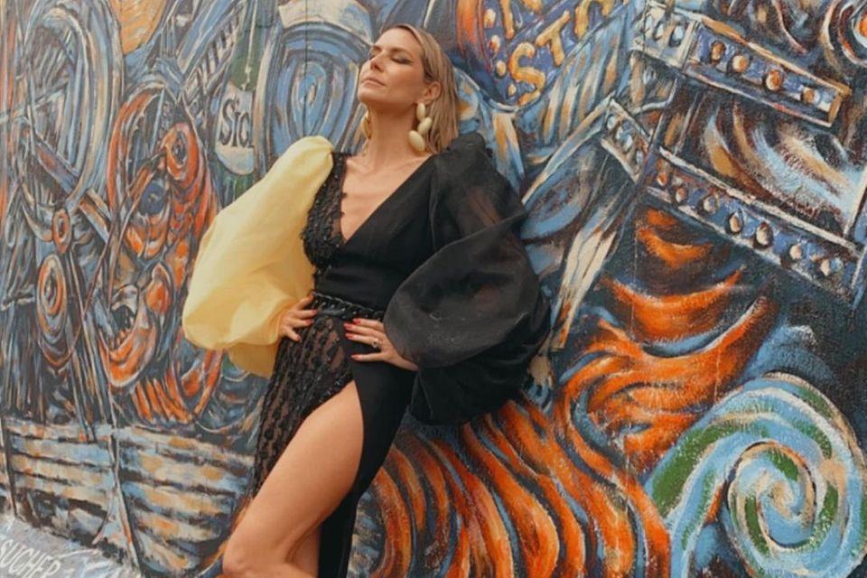 Das Kleid ist nicht nur wegen des hohen Beinschlitz ein absoluter Blickfang, opulente Ärmel in verschiedenen Farben, durchsichtige Einsätze und ein tiefer Ausschnitt machen Heidi Klum noch mehr zum Hingucker. Was wohl die Passanten dort dachten?