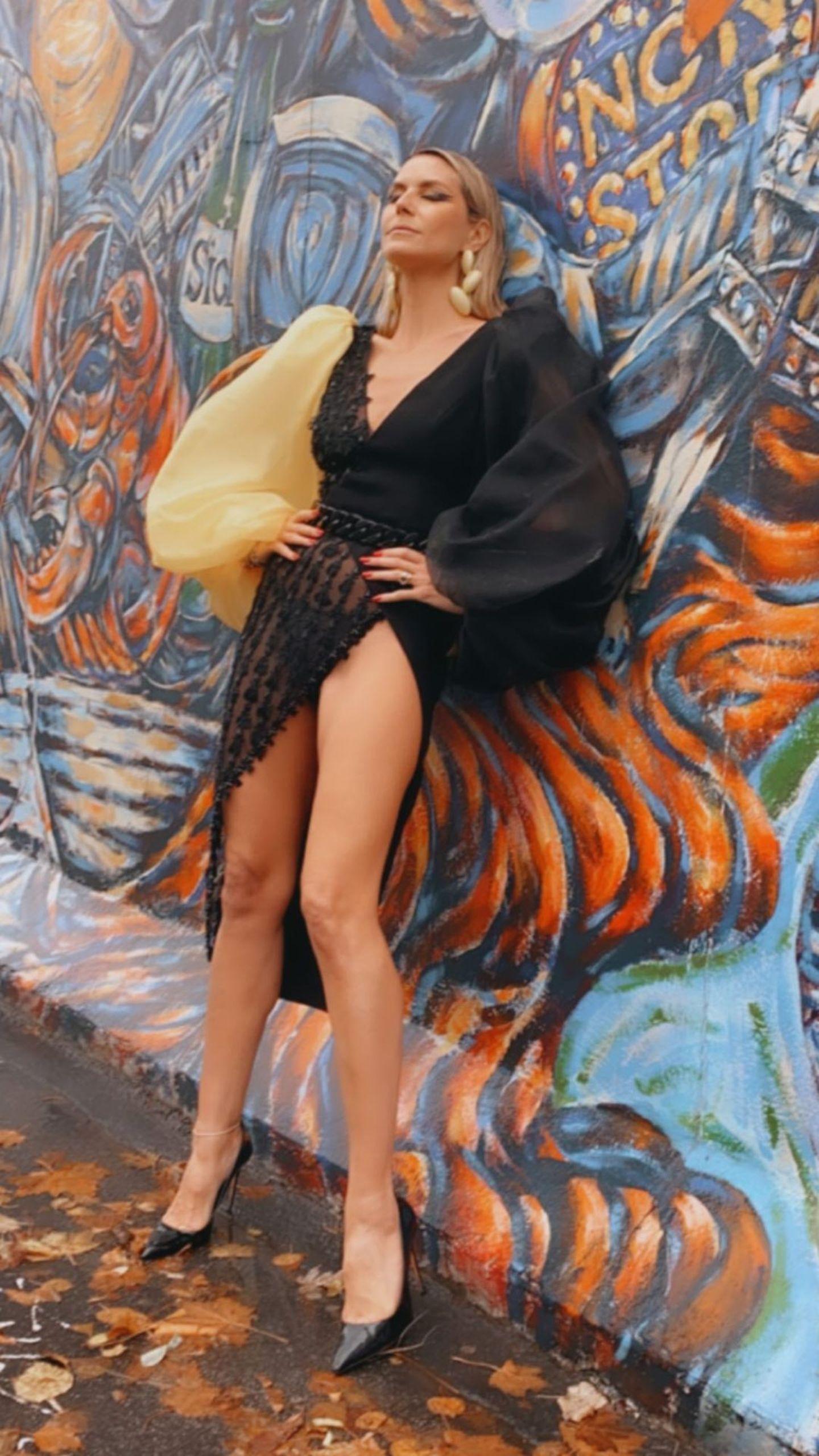 Bevorstehender Lockdown und regnerisches Herbstwetter halten Heidi Klum nicht davon ab, ein wenig Glamour nach Berlin zu bringen. In einer eleganten Robe von Georges Hobeika posiert sie lasziv an der Berliner Mauer.