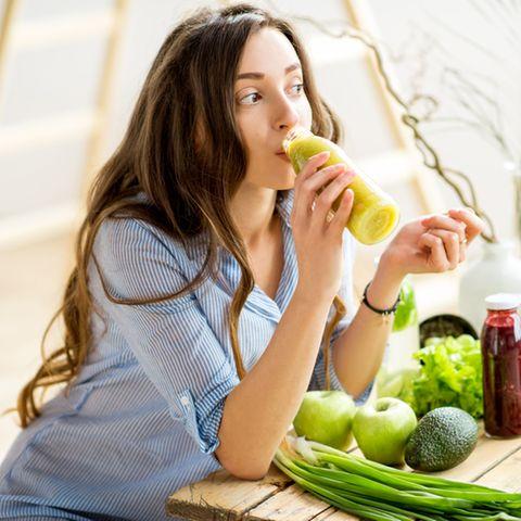 Brünette Frau trinkt grünes, gesundes Getränk zuhause