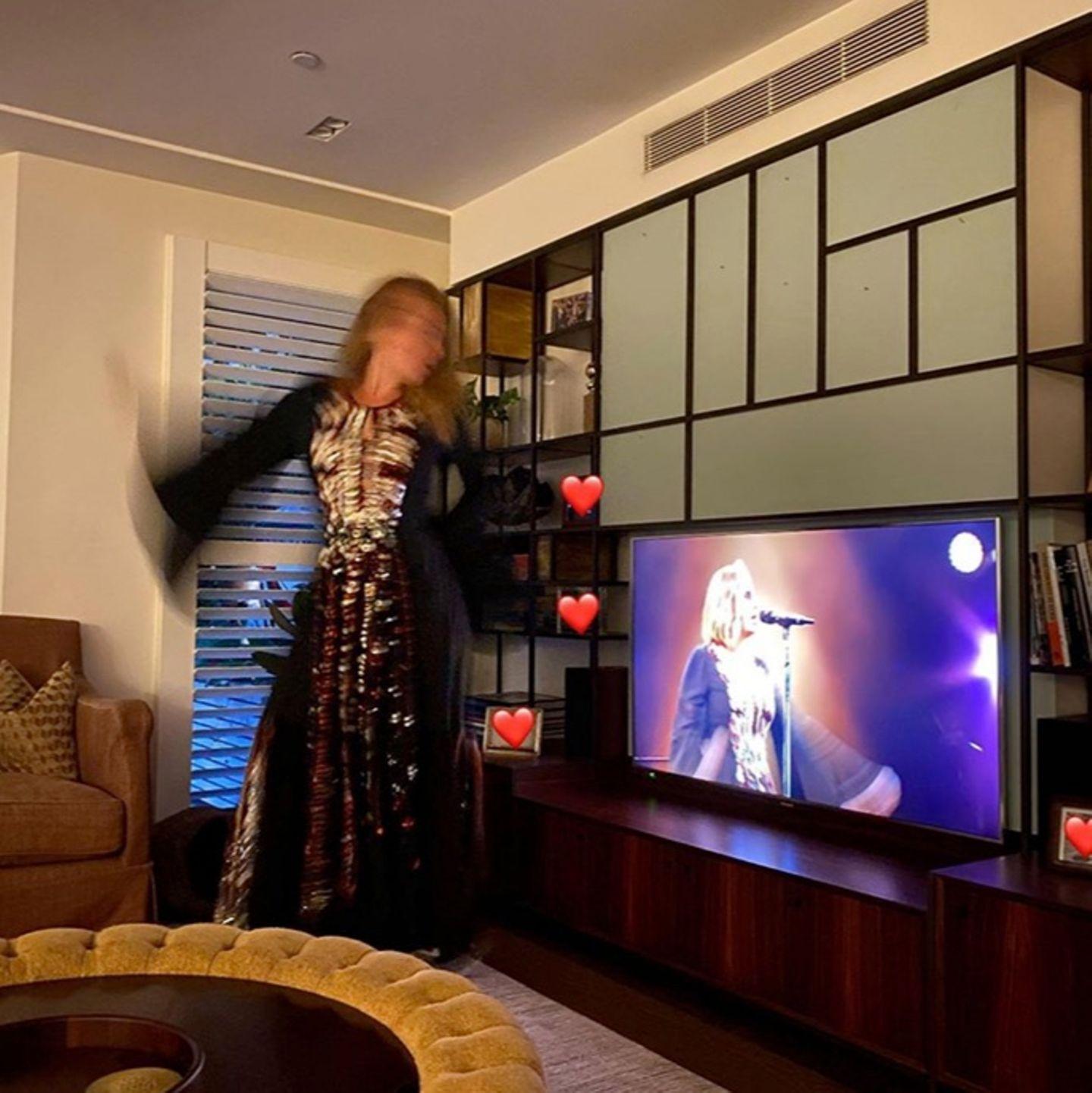 So sieht es also aus, wenn Adele zu ihren eigenen Auftritten abfeiert. Im Wohnzimmer tanzt die Sängerin ausgelassen, während wir einen Blick auf die opulente Wohnwand, den Wohnzimmertisch und auf einStück ihres Sofas erhaschen.