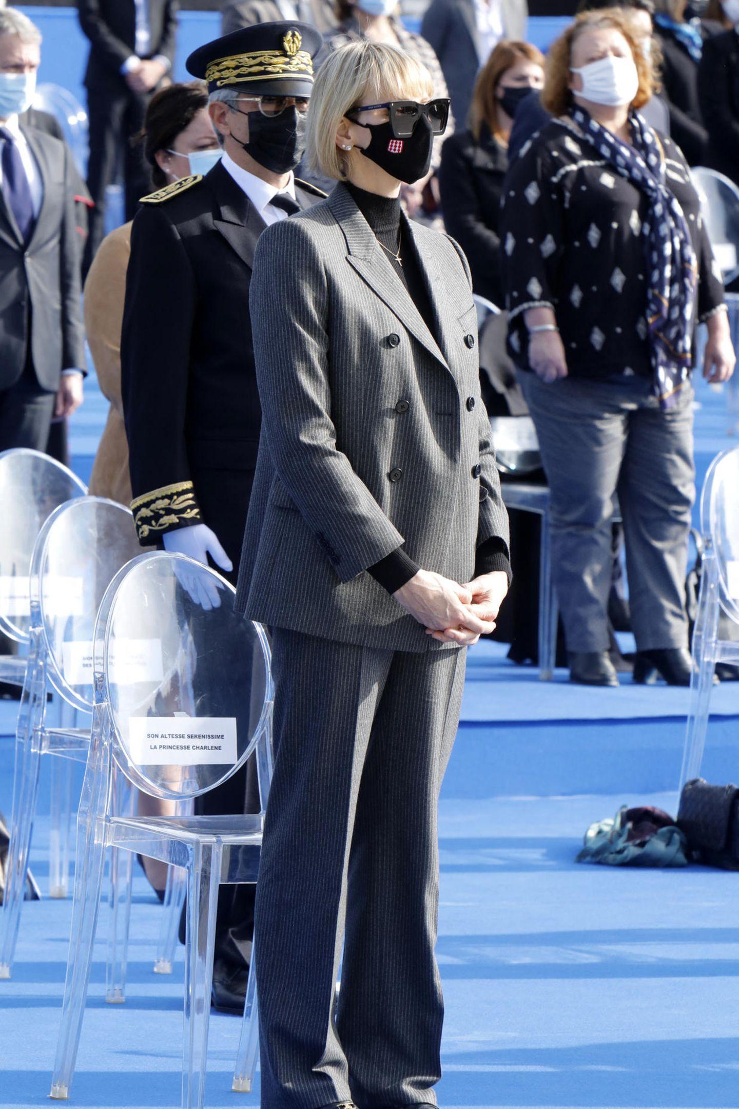 Mit einer dunklen XXL-Sonnenbrille und schwarzer Gesichtsmaske zeigt sich Fürstin Charlène während derEhrungszeremonie für die Opfer des Terroranschlags vom 29. Oktober 2020 auf dem Schlossberg in Nizza. Wir hätten die Frau von Prinz Albert auf den ersten Blick gar nicht erkannt. Denn im Inkognito-Look bestehend aus einem kastig-geschnittenen Blazer und passender Anzugshose mit auslaufendem Bein sowie einem schwarzen Rollkragenpullover hält sich die 42-Jährige optisch sehr bedeckt. Einzig und allein ihr markanter Pagenschnitt entlarvt die ehemalige Schwimmerindann doch.