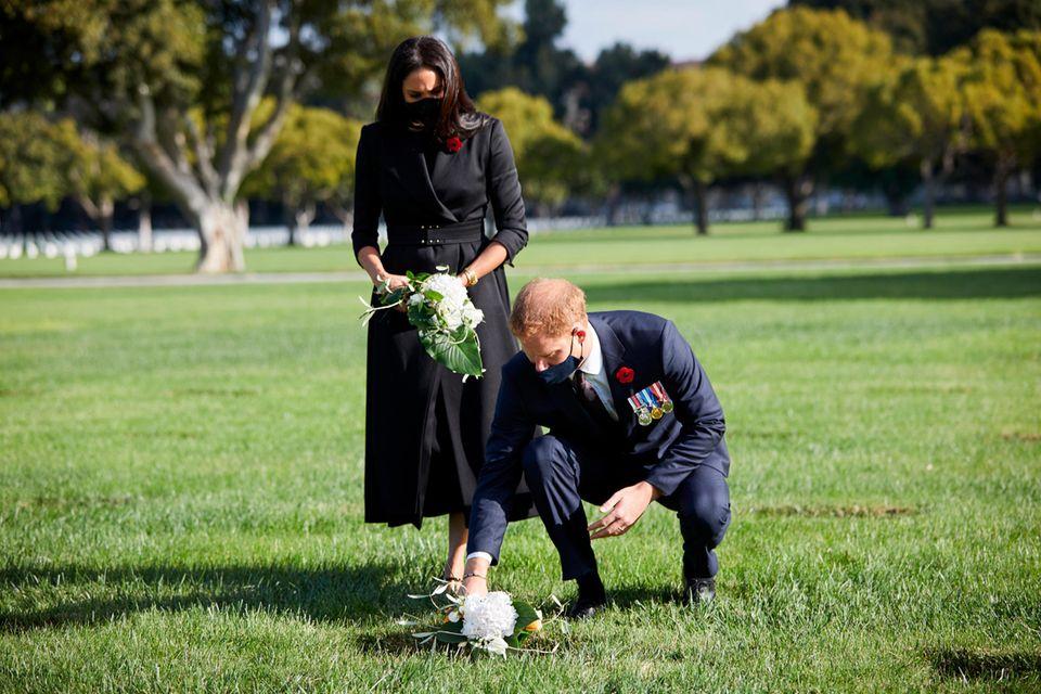 Das Paar legt Sträuße mit im eigenen Garten gepflückten Blumen nieder. Beide tragen Masken.