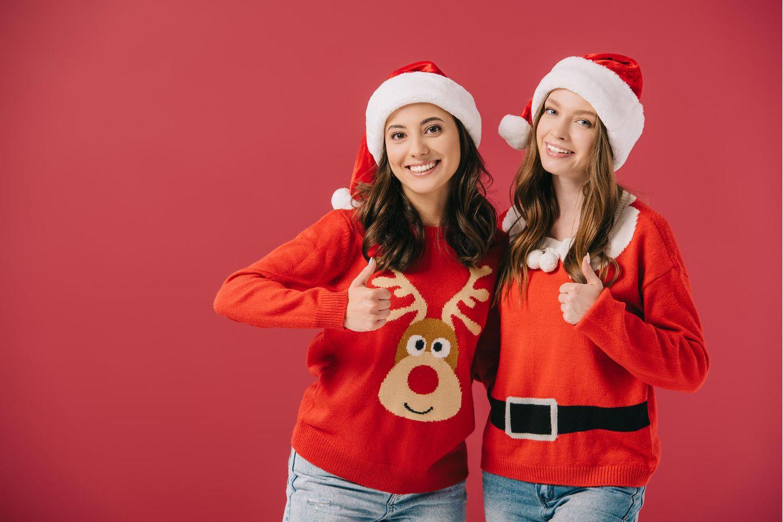 Weihnachtspullover, Ugly Christmas Sweater, zwei junge Frauen mit einem hässlichen Weihnachtspullover