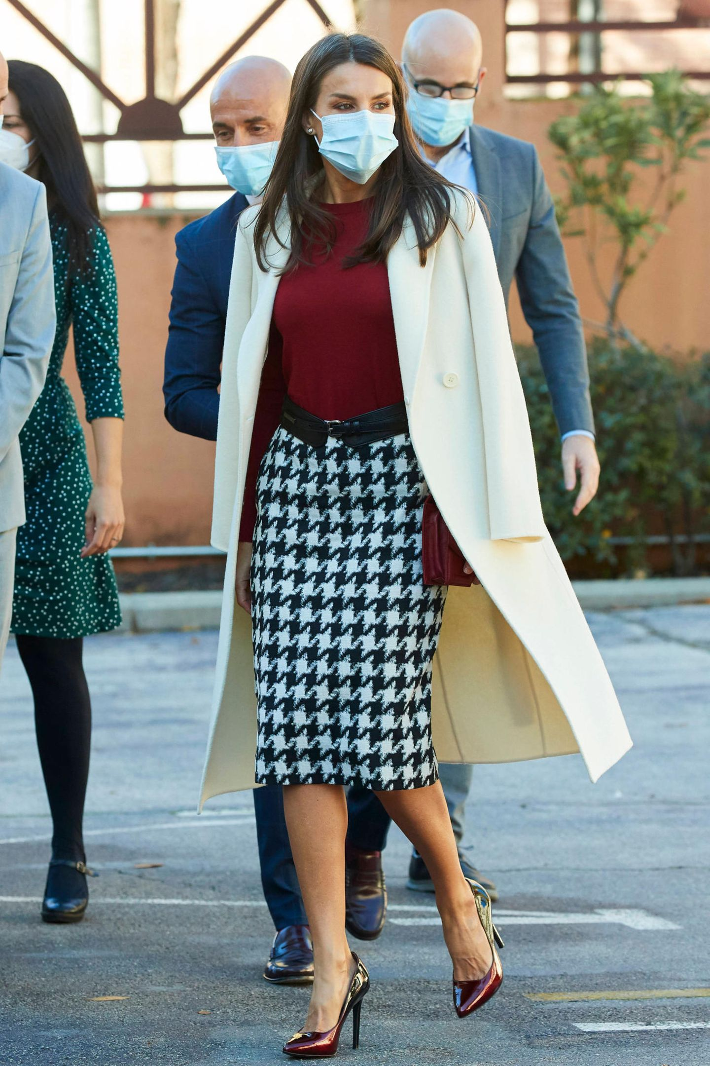 Königin Letizia erscheint in einer recht auffälligen Outfit-Kombination zu einem Arbeitstreffen in Madrid. Zu einem Pencilskirt mit Hahnentritt-Muster (kostet etwa 200 Euro) wählt die 48-Jährige einen dunkelroten Pullover für etwa 165 Euro, beides von Hugo Boss, und Pumps mit Farbverlauf in Lack-Optik von Lodi, Kostenpunkt: ca. 200 Euro. Ein schwarzer Taillengürtel und eine ebenfalls dunkelrote Clutch von Reliquiae für 525 Euro runden den Look stilvoll ab. Gewusst wie: Letizia legt sich ihrencremefarbenen Wollmantel lässig über die Schultern.