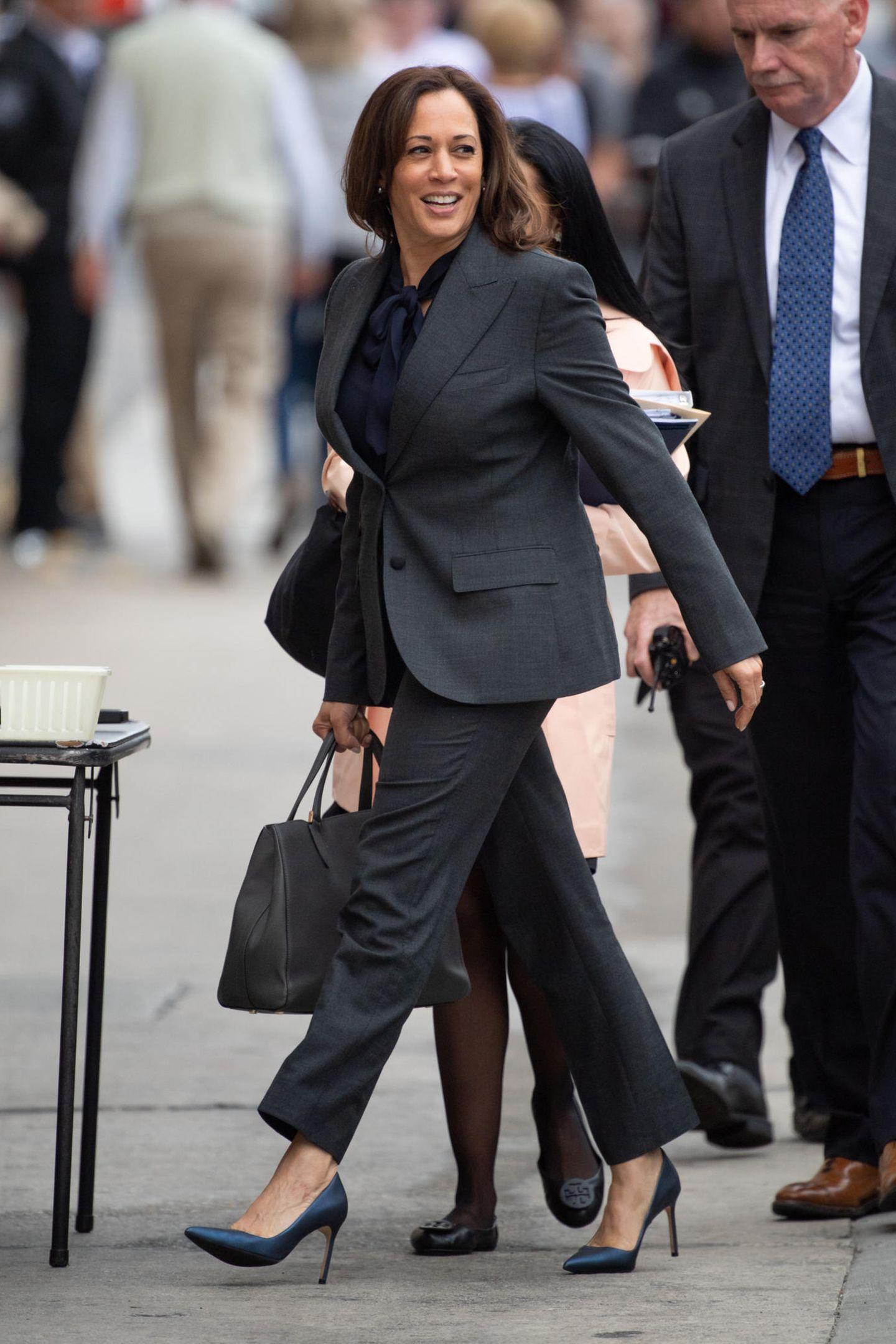 Entschlossenen Schrittes macht sich die 56-Jährige auf den Weg zur Fernseh-Show des US-Moderators Jimmy Kimmel, in der sie als Gast live auftreten wird. Ihr Power-Look besteht aus einem dunkelgrauen Anzug, den sie zu dunkelblauen High-Heels und einer ebenfalls dunklen Schluppenbluse kombiniert.