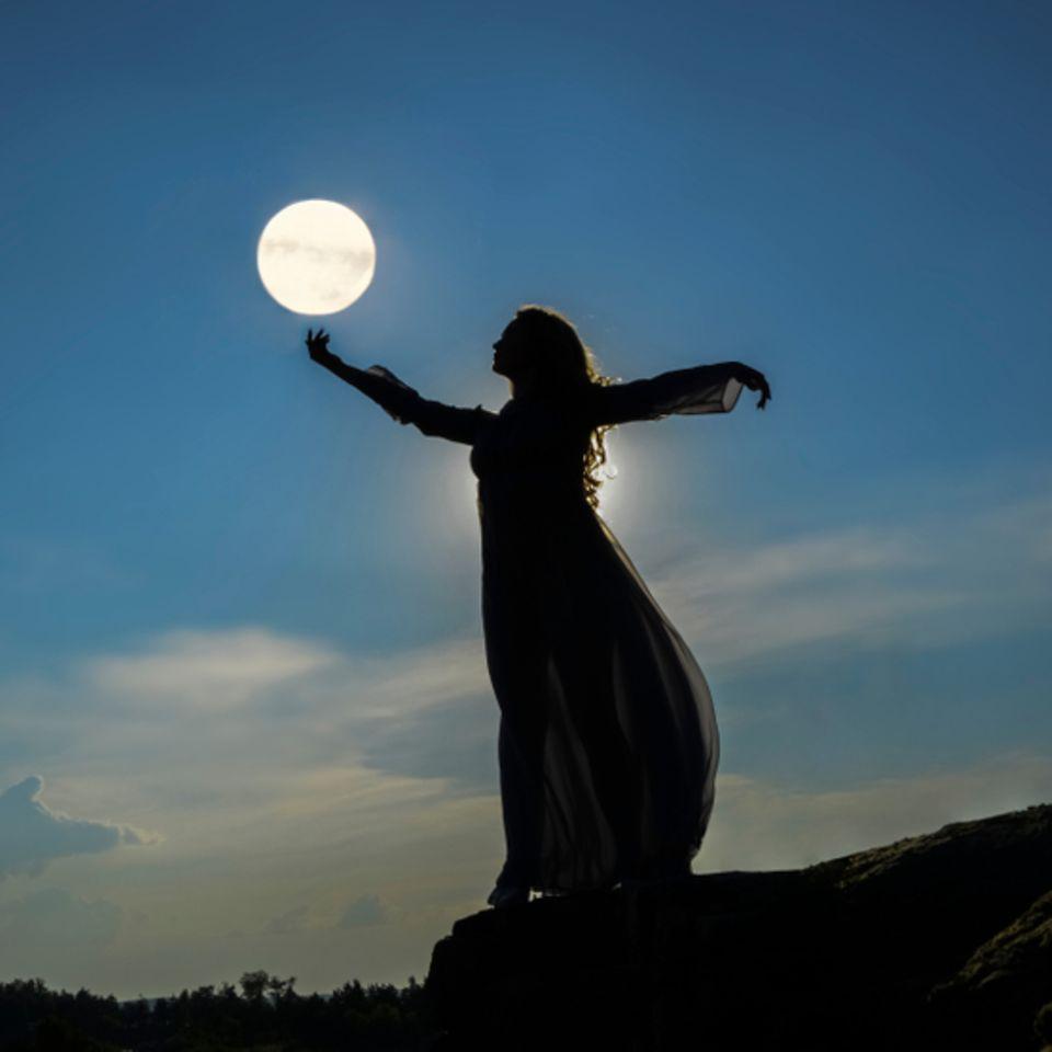 Mondzeichen: Die Silhouette einer Frau vor dem Abendhimmel.