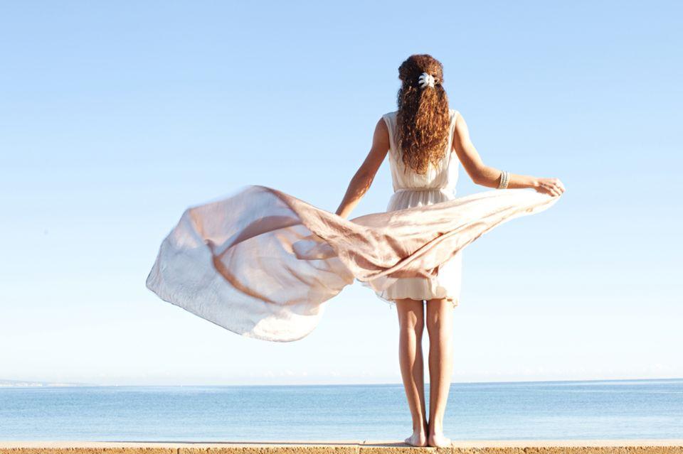 Luftzeichen: Frau mit langem Kleid, das im Wind weht.