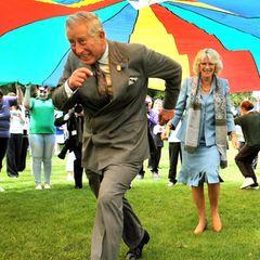 Da kommen Prinz Charles und Herzogin Camilla aber ins Schwitzen: Bei einem Besuch auf der britischen Kanalinsel Guernsey rennen die beiden unter einem riesigen Fallschirm durch.