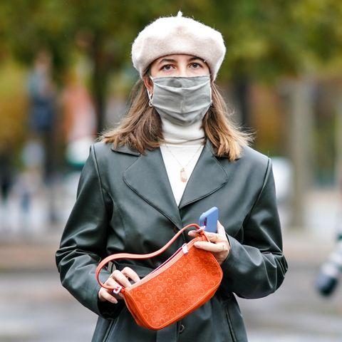 Fashionista mit Gesichtsmaske und Mütze vor der Chanel-Show