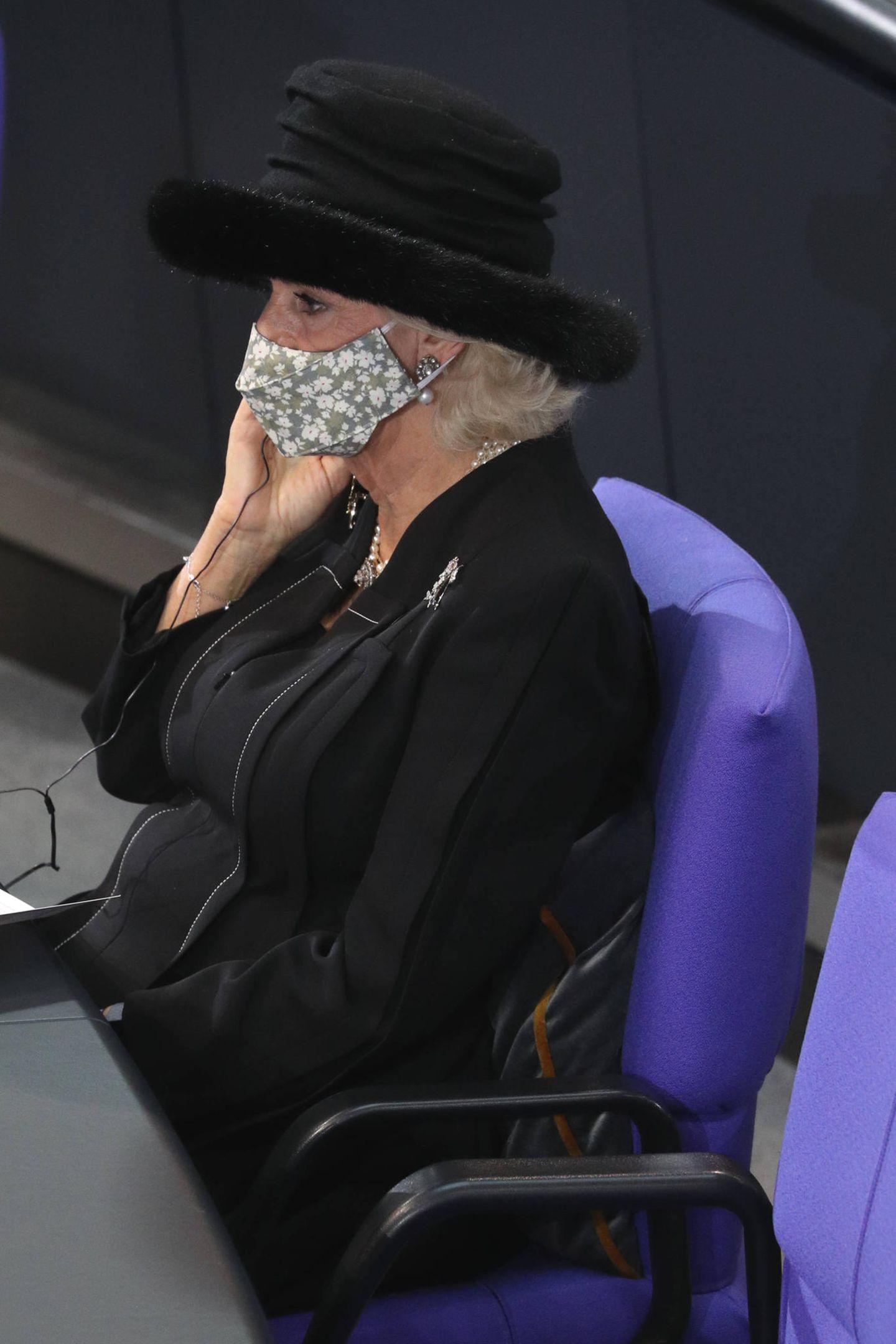 Unter den Zuhörern im Plenarsaal befindet sich auchHerzogin Camilla, die mit Hut und Maske interessiert den Worten ihres Gemahls lauscht.