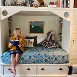 Nicht nur Reese ist eine kleine Leseratte, auch ihre drei Kinder bekommen regelmäßig vorgelesen. In einem weißen Holzschrank mit eingebautem Bett lässt es sich aber nicht nur gut zuhören, sondern auch toben. Die dicke Matratze mit Blumenmuster sorgt für die perfekte Polsterung, falls der Kopfstand nicht gelingen sollte.