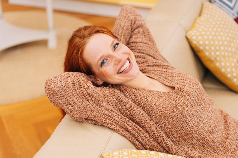 Ungeduld: Lächelnde Frau auf dem Sofa.