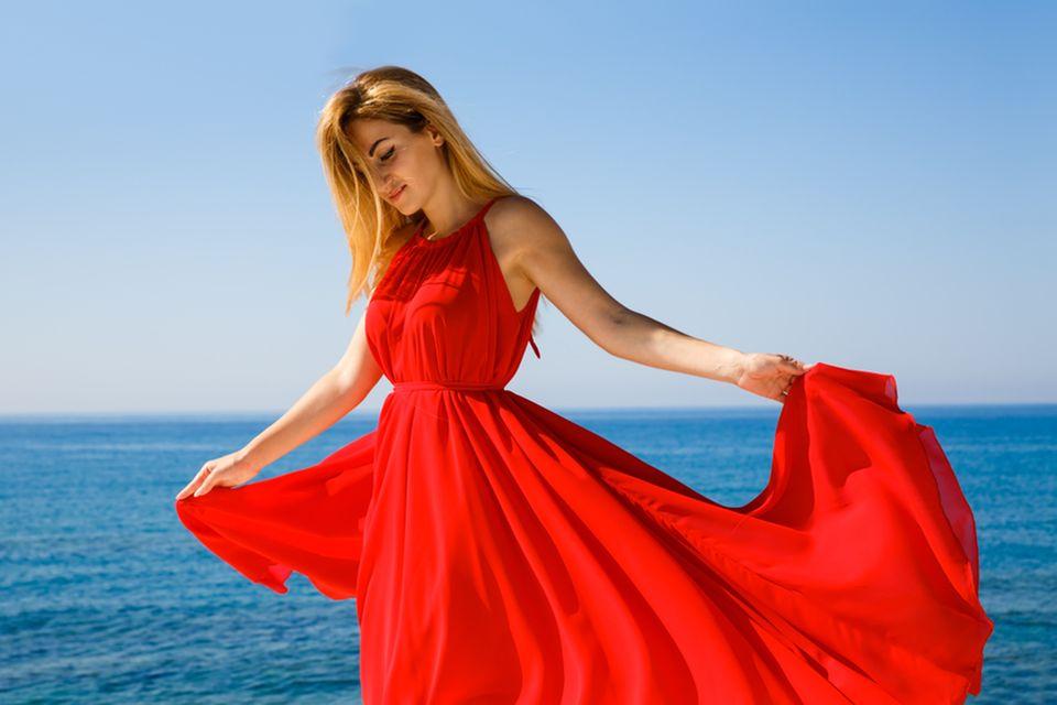 Venus-Zeichen: Frau mit einem roten langen Kleid