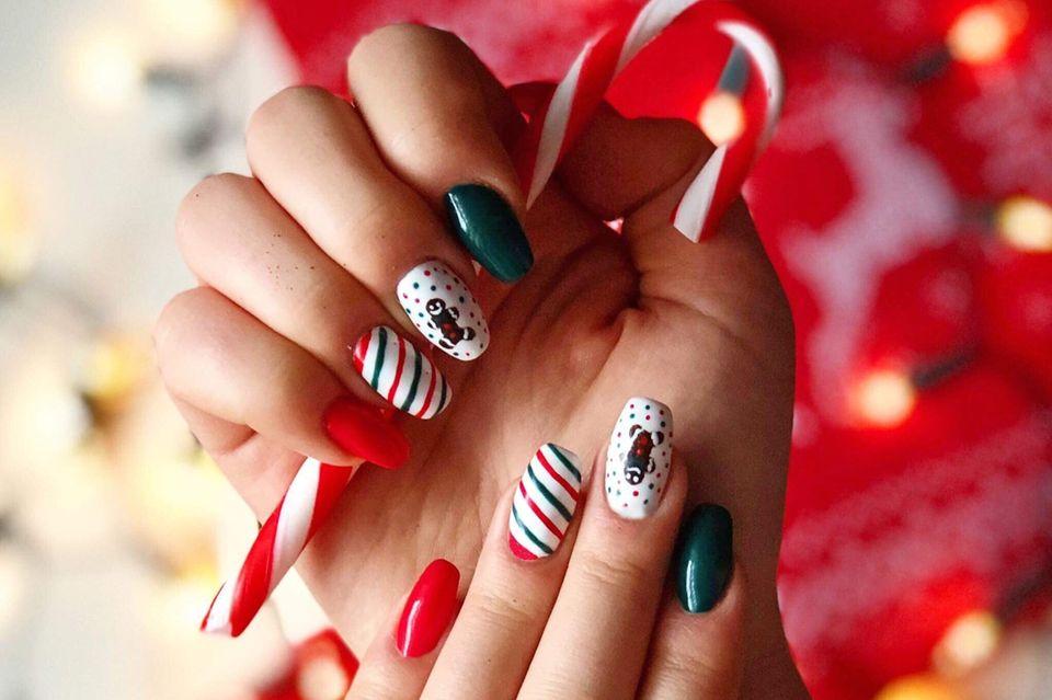 Weihnachtsnägel: Frau mit weihnachtlichen Motiven auf den Nägeln