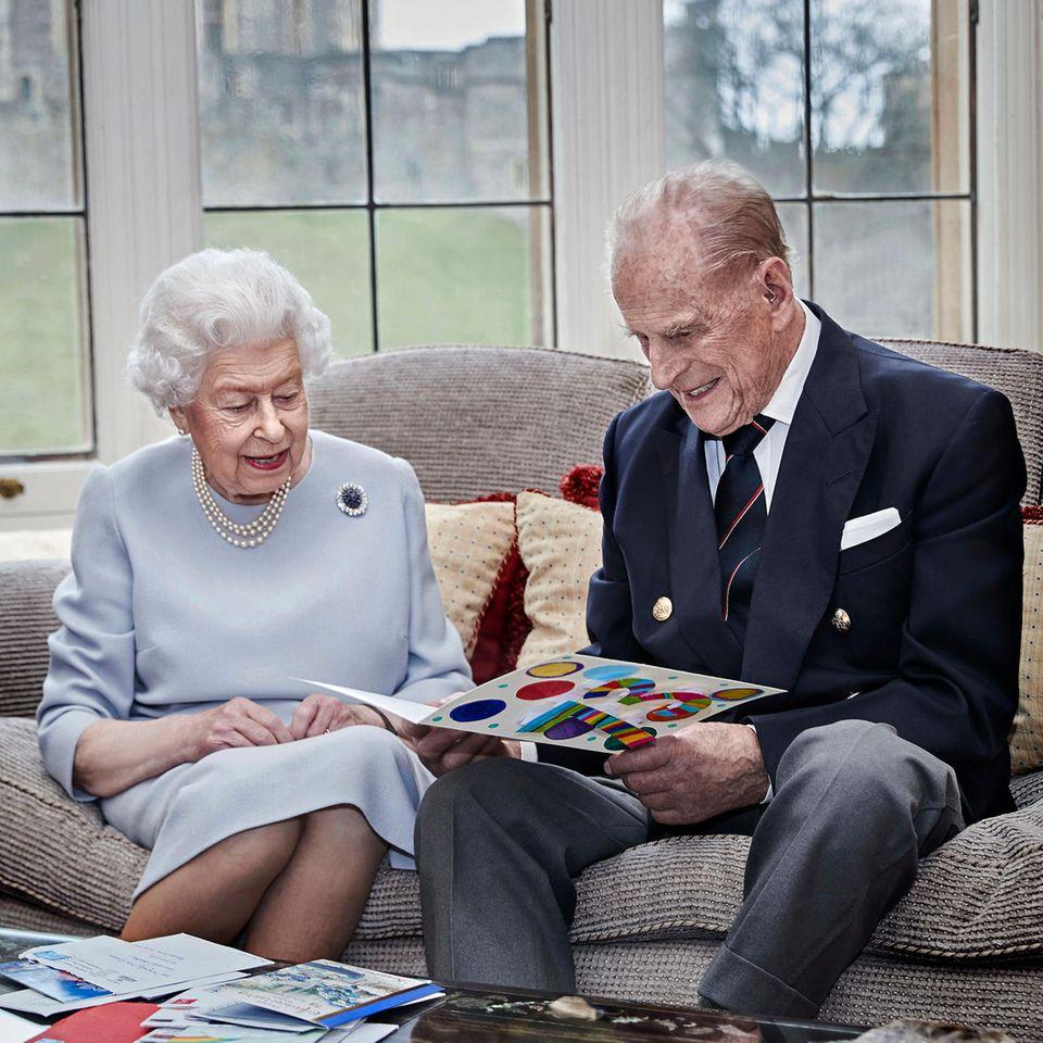 """20. November 2020  Congratulations! Queen Elizabeth und Prinz Philip sind bereits seit 73 Jahren verheiratet. Das Foto, das das britische Königshaus zum Hochzeitstag veröffentlicht, zeigt das Paar wenige Tage zuvor im """"Oak Room"""" auf Schloss Windsor. Vor ihnen liegen die ersten Glückwunschkarten, doch die Karte, die sie in den Händen halten, ist ein ganz besonders Geschenk: Ihre Urenkel Prinz George, Prinzessin Charlotte und Prinz Louis haben sie für sie gestaltet."""