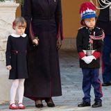 In ihren schicken Feiertagsoutfits wirken Prinzessin Gabriella und Prinz Jacques von Monaco fast ein bisschen verkleidet. Während Gabriella an der Hand von Mama Charlène ein blaues Kleid mit Bubikragen und eine weiße Strumpfhose trägt,zeigt sich der junge Prinz von Kopf bis Fuß in Uniform.