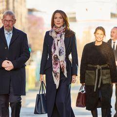 Prinzessin Mary ist anlässlich des Weltkindertags in Kopenhagen unterwegs. Sie trägt einen schicken dunklen Mantel von Fonnesbech, einem nachhaltigen dänischen Label, Stiefeletten des spanischen Labels Pura Lopez und eine dunkle Leder-Handtasche von Prada. Als farbigen Eyecatcher wählt sie ein gemustertes Tuch.