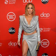 Sie darf natürlich auch nicht fehlen: Sängerin Jennifer Lopez kommt dem unausgesprochenen Dresscode nach und wählt ebenfalls ein silberfarbenes Glitzer-Oberteil mit Wasserfall-Ausschnitt und einem farblich passenden Rock mit XXL-Beinschlitz.