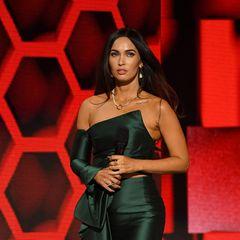 """Bei den American Music Awards sorgt Megan Fox gleich mehrfach für Staunen: Es ist ihr erster gemeinsamer Auftritt mit Neu-Boyfriend Machine Gun Kelly. Dazu entdecken Fans ein neues Tattoo auf ihrem Schlüsselbein. """"El Pistolero"""" steht dort in verschnörkelter Schreibschrift. Etwa ein Liebestattoo für ihren Freund, in den sie sich im spanischsprachigen Costa Rica verliebte? Gut möglich, denn auf dem Interlude-Track """"Banyan Tree"""" des Musikers hört man Fox sagen: """"Du hast meine Initialen auftätowiert, ich mir deinen Spitznamen."""""""