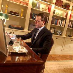 """Konzentriert sitzt Prinz Daniel an seinem Schreibtisch in seinem Arbeitszimmer auf Schloss Haga und nimmt über seinen Laptop an einem Treffen mit der """"En Frisk Generation""""-Gesundheitsorganisation teil. Vorbildlich steht eine Karaffe mit Wasser griffbereit."""